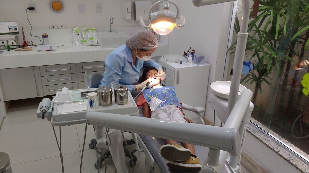 детский хирург лечит зубы ребенку